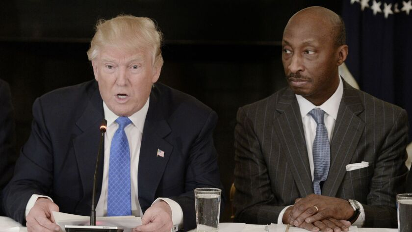 President Trump meets with Merck Chief Executive Kenneth Frazier, right, in February 2017. Frazer quit Trump's executive advisory group to protest Trump's response to the Charlottesville racist attack, but Merck later offered Trump a fig leaf on drug pricing.