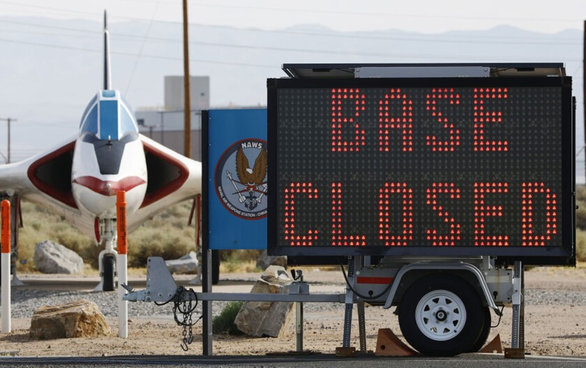 A sign posted July 7 outside the main gate of the China Lake naval station in Ridgecrest, Calif., shows the base is closed.