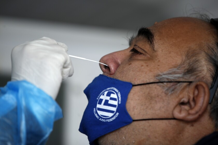 """A medical staff member from the National Health Organization (EODY) conducts a rapid COVID test on a man, wearing a face mask with the Greek flag, in Athens, Thursday, Nov. 5, 2020. Greek Prime Minister Kyriakos Mitsotakis has announced a nationwide three-week lockdown starting Saturday morning, saying that the increase in the coronavirus infections must be stopped before Greece's health care system comes under """"unbearable"""" pressure. (AP Photo/Thanassis Stavrakis)"""