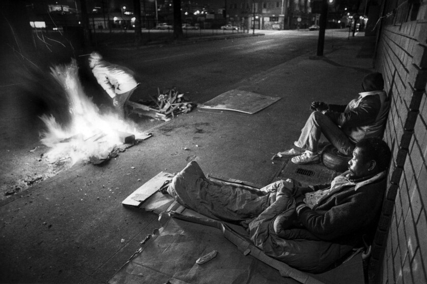 Dec. 28, 1988: Two homeless men sit against a wall on Towne Street in downtown Los Angeles as a woman warms herself near an open fire.