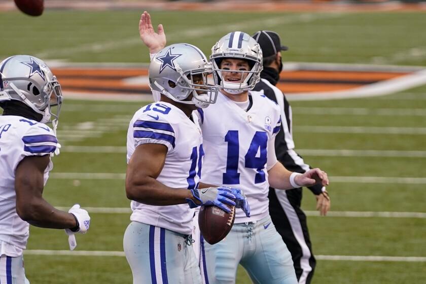 Dallas Cowboys quarterback Andy Dalton (14) celebrates a touchdown throw with wide receiver Amari Cooper (19) in the first half of an NFL football game against the Cincinnati Bengals in Cincinnati, Sunday, Dec. 13, 2020. (AP Photo/Bryan Woolston)