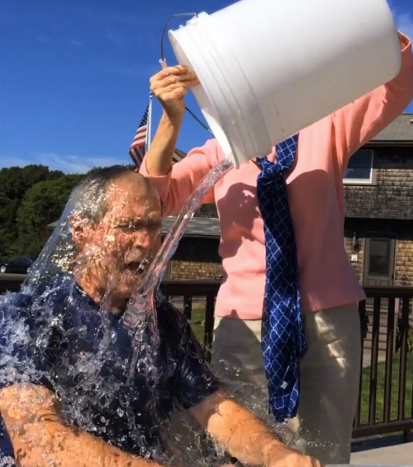 In this image from a video posted on Facebook, courtesy of the George W. Bush Presidential Center, former President George W. Bush participates in the Ice Bucket Challenge with the help of his wife, Laura Bush, in Kennebunkport, Maine.