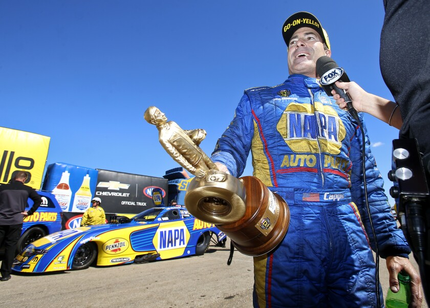 FILE- In this May 21, 2017, file photo, funny car driver Ron Capps is interviewed by Fox Sports after winning the NHRA Heartland Nationals in Topeka, Kan. Don Schumacher Racing has won the last 14 events in the NHRA's Funny Car division. It's a record for the racing series. (Chris Neal/The Topeka Capital-Journal via AP, File)