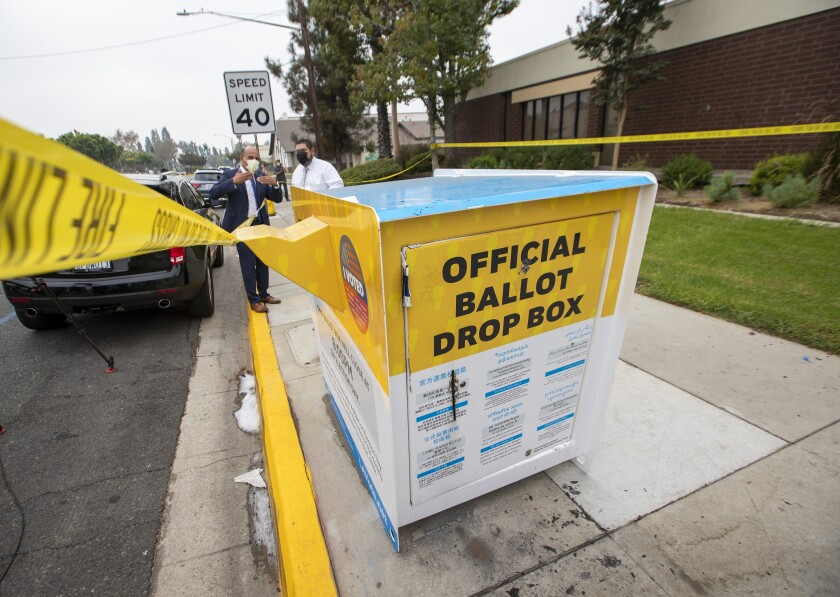 Officials in Baldwin Park inspect the fire-damaged ballot drop box on Oct. 19.