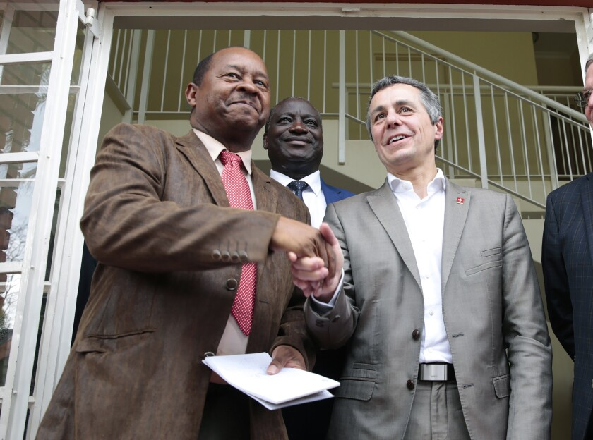 FILE — In this Jan. 9, 2019 file photo Federal Councilor Ignazio Cassis, right, of Switzerland, shakes hands with Zimbabwean Health Minister, Obadiah Moyo, left, in Harare. Moyo, who appeared in court Saturday, June 20, 2020 was arrested Friday by the Zimbabwe Anti-Corruption Commission and is accused of illegally awarding a $42 million tender to a company for a supply of COVID-19 drugs and personal protective equipment while aware the company was not a pharmaceutical supplier but a consultancy firm. (AP Photo/Tsvangirayi Mukwazhi, File)