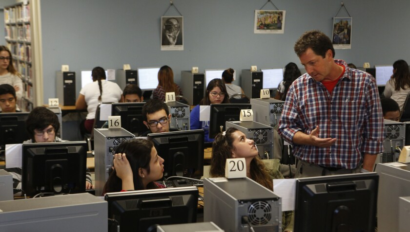 Technology coordinator Michael Sinclair talks with 11th-grade students at Francisco Bravo Senior High Medical Magnet School practicing for state standardized tests in 2015.