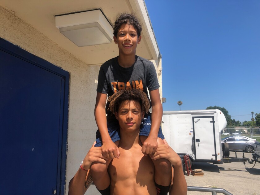 Reseda receiver Dranel Rhodes holds up his 12-year-old brother, Amari. They have an older brother who played for the Regents and are part of the tradition of younger brothers staying in the Reseda program.