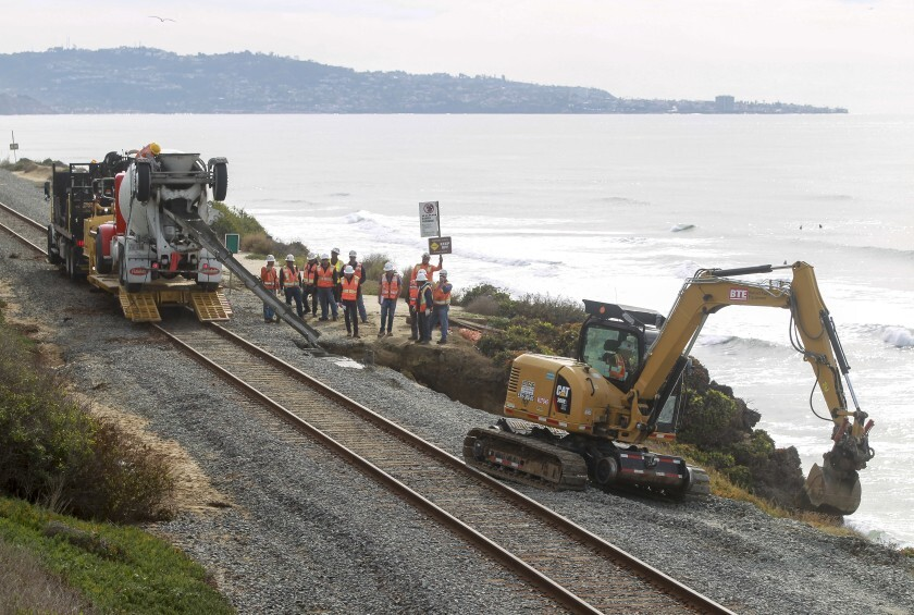 Workers repair erosion Nov. 30 caused by the recent rains on the bluffs next to the railroad tracks in Del Mar.