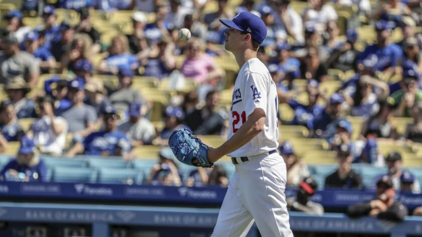 Pitcher Walker Buehler tosses the ball in apparent frustration during the fourth inning of the Dodgers' 8-7 victory over the Arizona Diamondbacks on Sunday.