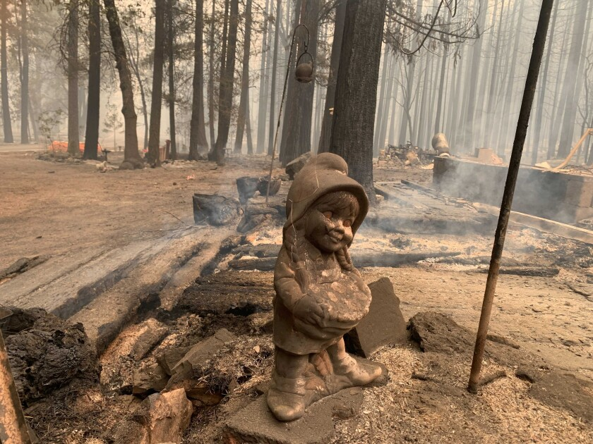 A surviving ceramic statue is seen outside a house that burned along North Arm Road in Plumas County near Taylorsville, Calif., Sunday, Aug. 15, 2021. Thousands of Northern California homes remain threatened by the nation's largest wildfire and officials warn the danger of new blazes erupting across the West is high because of unstable weather. (AP Photo/Eugene Garcia)