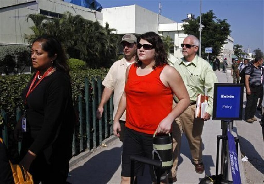 Charisa Coulter, second from right, of Meridian, Idaho, one of two US Baptist missionaries held on kidnapping charges in Haiti, arrives to the airport, accompanied by US embassy staff, after her release from jail in Port-au-Prince, Monday, March 8, 2010. Coulter was set free more than a month after she and nine other Americans were arrested for trying to take 33 children out of Haiti without proper documents after the Jan. 12 earthquake. Laura Silsby, the leader of the Idaho-based missionaries, remains detained. (AP Photo/Esteban Felix)
