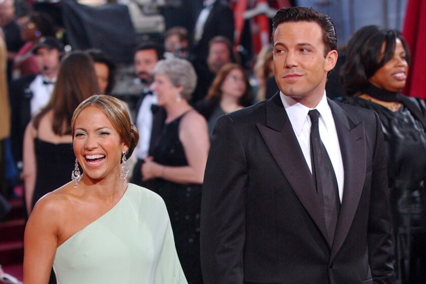 Jennifer Lopez in a one-shouldered gown and Ben Affleck in a dark suit