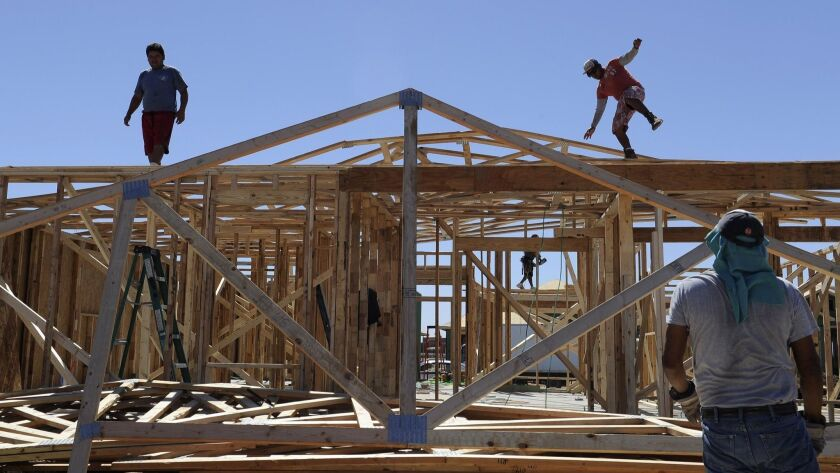 FILE - In this Sept. 24, 2013, file photo, a man steadies himself as he and others work on framing n