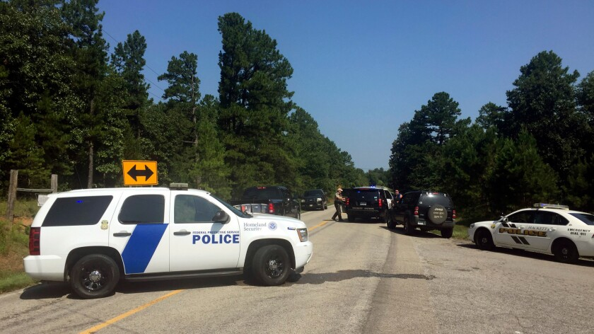 Law enforcement officials block an intersection during a standoff after two officers were shot in western Arkansas on Wednesday.