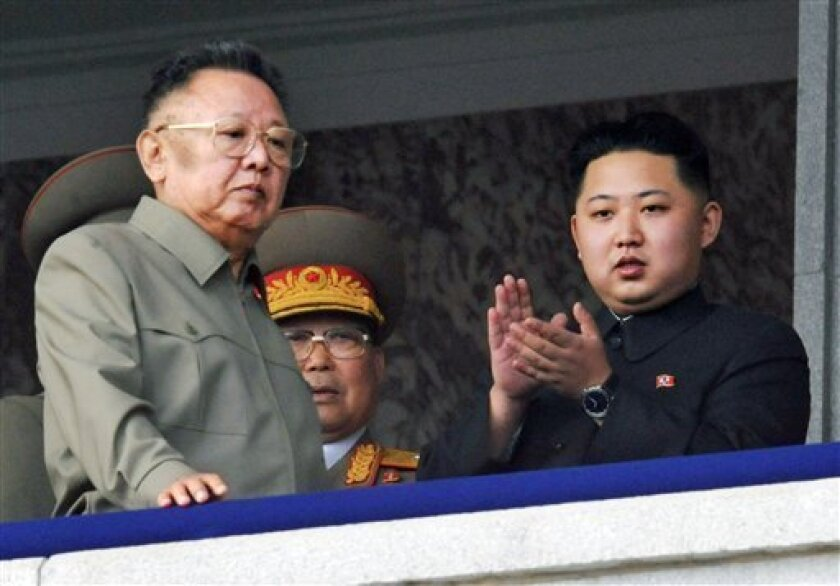 FILE - In this Oct. 10, 2010 file photo North Korea leader Kim Jong Il, left, walks by his son Kim Jong Un on the balcony as they attend a massive military parade marking the 65th anniversary of the communist nation's ruling Workers' Party in Pyongyang, North Korea . If North Korea is planning a big birthday bash for its next leader, it's being kept well under wraps. Kim Jong Un, the young son unveiled to the world last year as leader Kim Jong Il's choice to succeed him as head of the communist nation of 24 million, is believed to be turning 28 on Saturday Jan. 8, 2011. But secretive North Korea has never confirmed his age or birth date _ or even that he's Kim Jong Il's son. (AP Photo/Kyodo News)