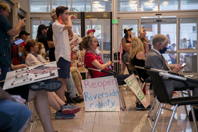 Residents who want public health orders rescinded crowd together in the lobby to watch video monitors of an emergency Riverside County Board of Supervisors meeting Friday at the County Administrative Center.