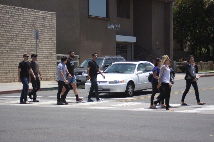 A group of pedestrians in a Village crosswalk
