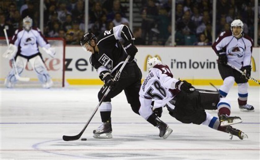 Los Angeles Kings center Trevor Lewis (22) gets caught up with Colorado Avalanche left wing Patrick Bordeleau (58) during the first period of a preseason NHL hockey game Saturday, Oct. 1, 2011, in Las Vegas. (AP Photo/Eric Jamison)