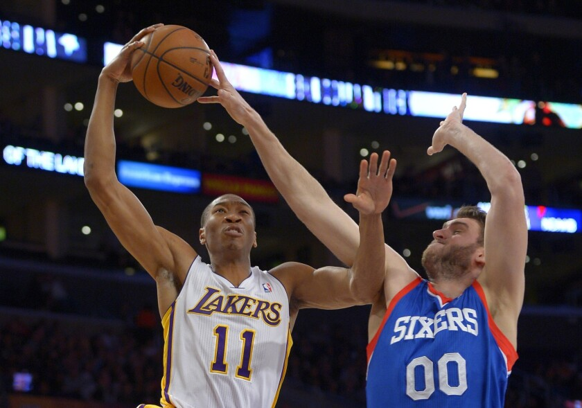 Philadelphia 76ers center Spencer Hawes, right, blocks a shot by Lakers guard Wesley Johnson during the first half of a game at Staples Center.