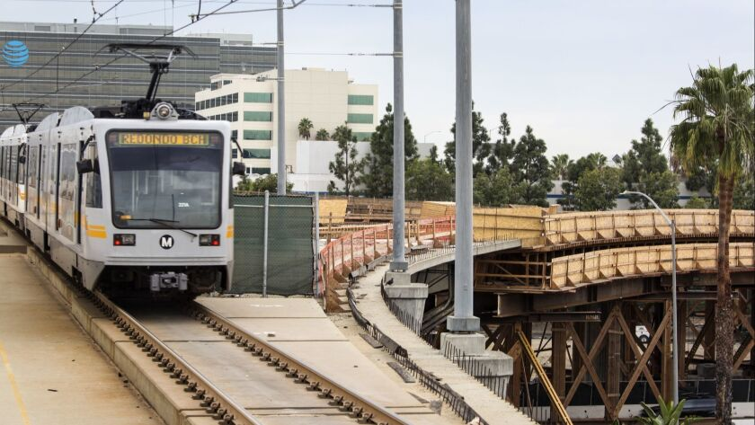 A Metro Green Line train leaves the Aviation/LAX station in El Segundo in 2016. The new Crenshaw Line will meet the Green Line near this stop, but transit officials are at odds over how to run trains along the junction shown to the right.