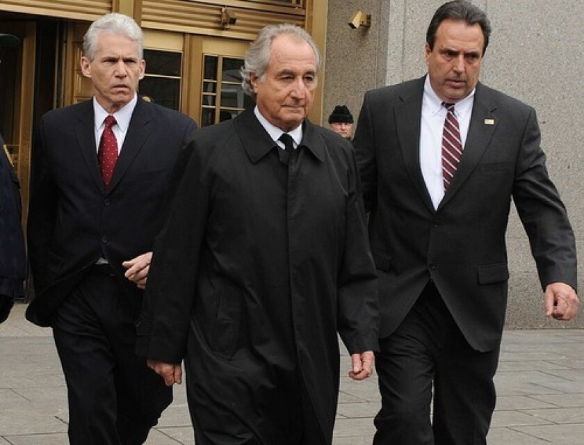 Bernard Madoff, center, leaves a New York federal courthouse.