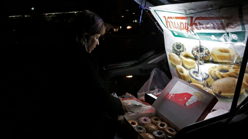 Sonia Garcia sells Krispy Kreme doughnuts, purchased across the border in El Paso, from the trunk of her car on a busy street in Ciudad Juarez, Mexico. The money she and her family make selling doughnuts helps pay for her son to go to college.