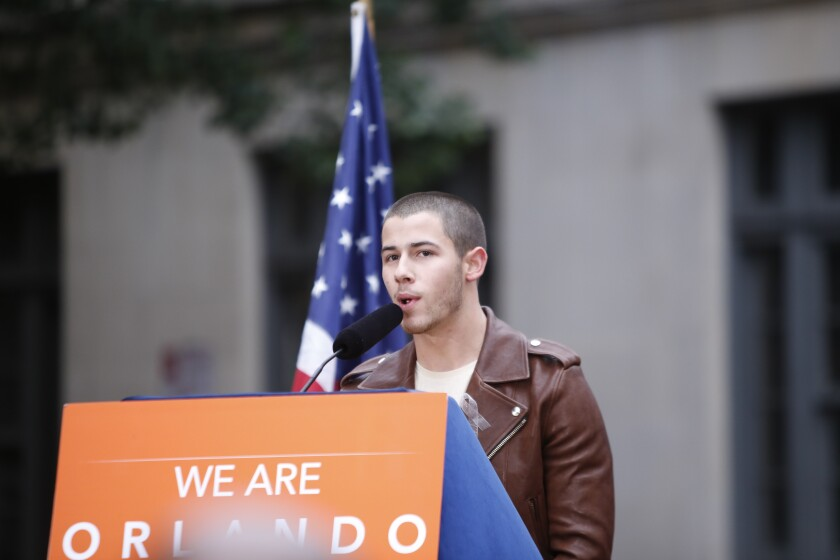 """Nick Jonas speaks at a lectern with the words """"WE ARE ORLANDO"""" on it."""