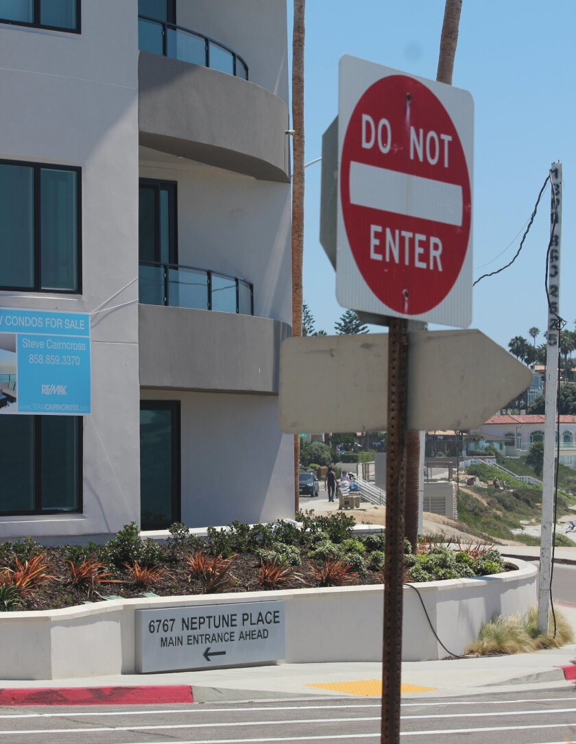 Signage on the three-story One Neptune condo project points the wrong way up Plaza del Norte.