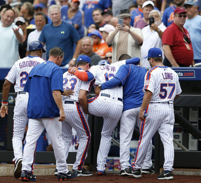 New York Mets first base coach Tom Goodwin, left, bench coach Dick Scott, center, and a team trainer, second from right, help Asdrubal Cabrera off the field after Cabrera doubled over  after scoring on Neil Miller's  first-inning RBI-triple during a baseball game against the Colorado Rockies, Sunda