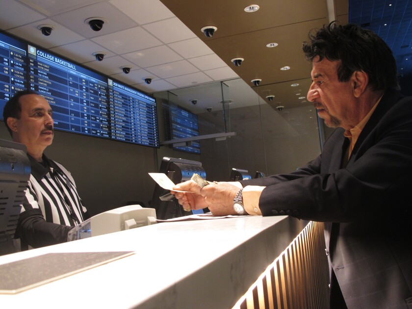In this Jan. 29, 2020 photo, a gambler makes a sports bet at Bally's casino in Atlantic City, N.J. On Friday, Nov. 13, 2020, New Jersey gambling regulators released figures showing that the state's red-hot sports betting market had set a new national record for the most money wagered on sports for the third month in a row, taking in over $803 million worth of bets. (AP Photo/Wayne Parry)