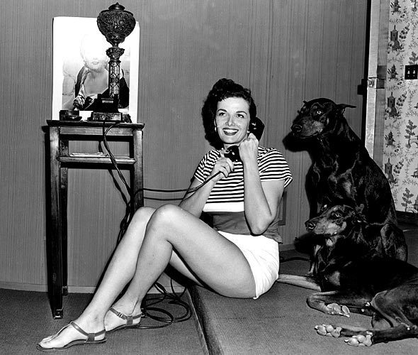 Jane Russell answers the phone in 1949 in her newly built home in the San Fernando Valley, where she and her husband lived with their two Dobermans. See full story