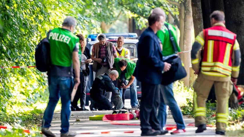 Members of a bomb disposal team check items at the scene where a knife-wielding man attacked passengers on a bus July 20 in Luebeck, Germany. Authorities feared a bag belonged to the attacker and could contain explosives.