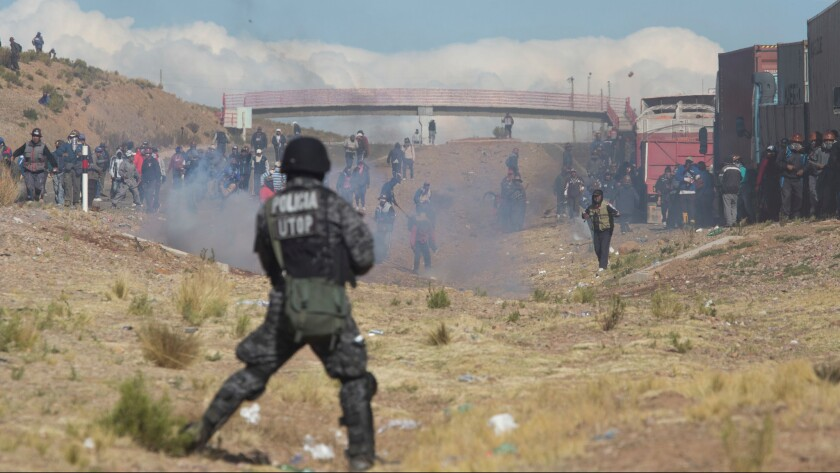 Miners clash with the police as they run from clouds of tear gas during protests in Panduro, Bolivia, on Thursday.
