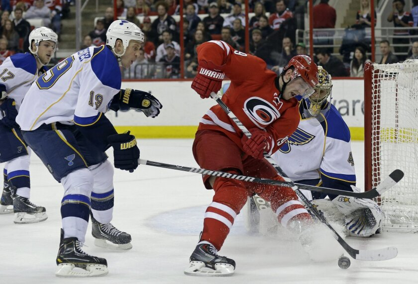 Carolina Hurricanes' Jiri Tlusty, second from right, of the Czech Republic, tries to score against St. Louis Blues goalie Jaroslav Halak (41) as Jay Bouwmeester (19) defends during the second period of an NHL hockey game in Raleigh, N.C., Friday, Jan. 31, 2014. (AP Photo/Gerry Broome)