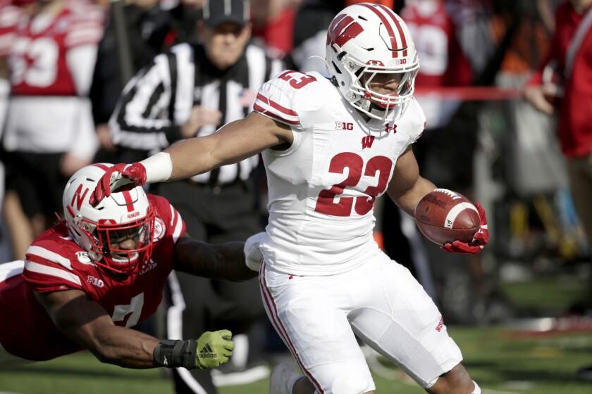 Wisconsin running back Jonathan Taylor carries the ball in front of diving Nebraska linebacker Mohamed Barry.