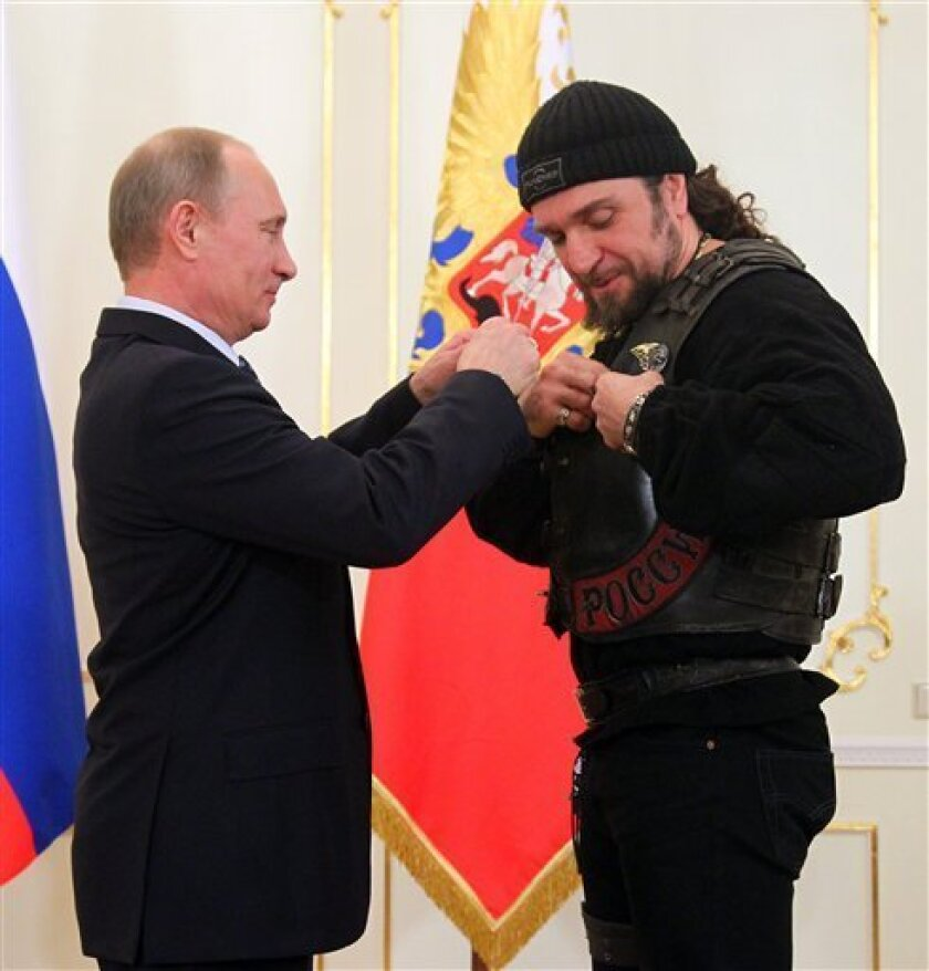 Russian President Vladimir Putin, left, presents a medal to Alexander Zaldostanov, a leader of Russian bikers movement, at his meeting with members of the Military History Society in the Novo-Ogaryovo residence outside Moscow, Thursday, March 14, 2013. (AP Photo/RIA-Novosti, Mikhail Klimentyev, Pre