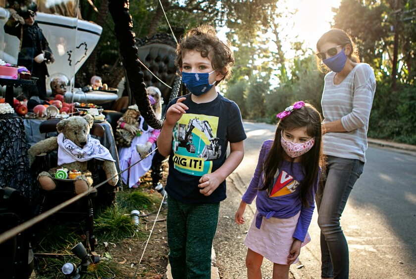 A family wears face coverings Wednesday while visiting a Brentwood home that goes all out with Halloween decorations.