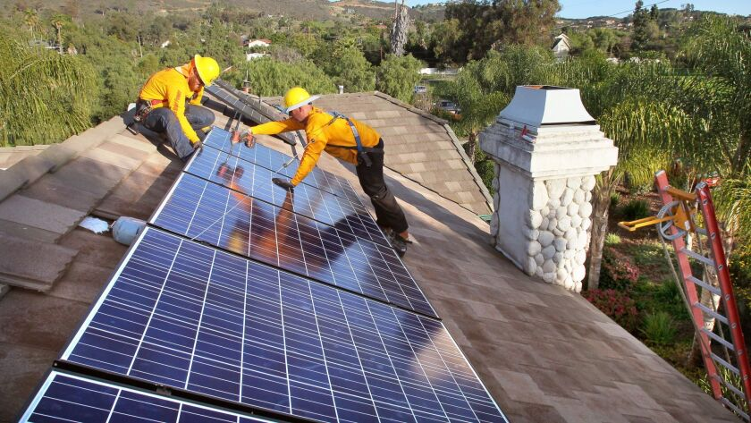 In a file photo, workers install solar panels on the roof of a home in Vista. |_Mandatory Photo Credit: Photo by Charlie Neuman/UT San Diego/Copyright 2014 San Diego Union-Tribune, LLC