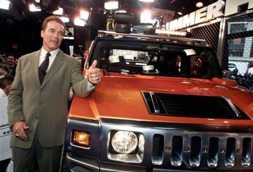 FILE - In this April 10, 2001 file photo, Arnold Schwarzenegger poses with a 2001 concept Hummer H2 at the utility vehicle's unveiling in New York's Times Square. The Hummer, the beefy, military-inspired SUV _ a macho icon for fans like Schwarzenegger and a symbol of ruin for environmentalists _ was done in by high gas prices and bad economic times. Unless a last-minute buyer steps forward, Hummer is going the way of Saturn and Pontiac. (AP Photo/Richard Drew, File)