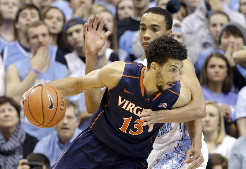 North Carolina's Brice Johnson, rear, pressures Virginia's Anthony Gill (13) during the first half of an NCAA college basketball game in Chapel Hill, N.C., Monday, Feb. 2, 2015. (AP Photo/Gerry Broome)