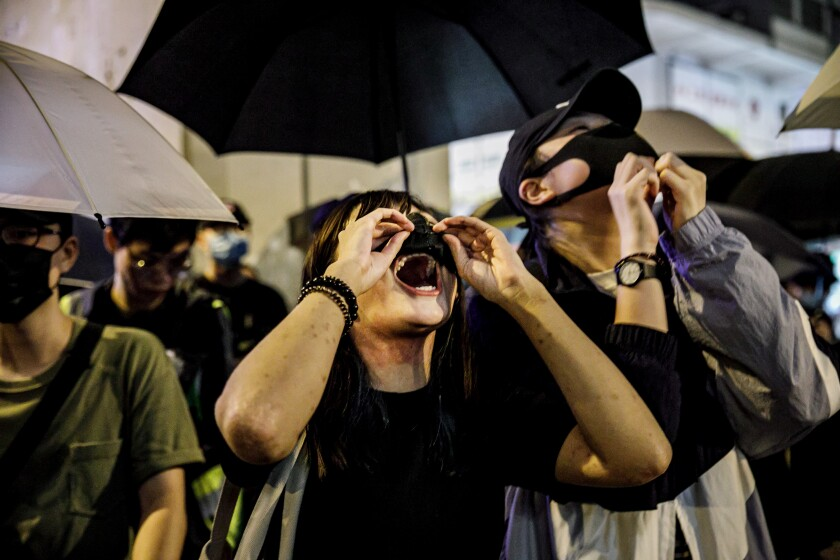 Protesters adjust their face masks to chant during a rally Sept. 2 in Hong Kong. At least a dozen mainlanders have been held or threatened by Chinese authorities after having participated in the Hong Kong demonstrations.