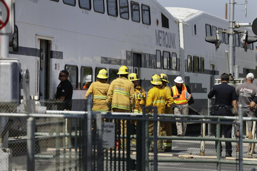 Firefighters gather outside a Metrolink train as they survey the scene of a collision between the train and a vehicle Tuesday, Sept. 6, 2016, in Los Angeles. Paramedics evaluated passengers on the Southern California commuter train that stopped after striking a vehicle on the tracks Tuesday, author