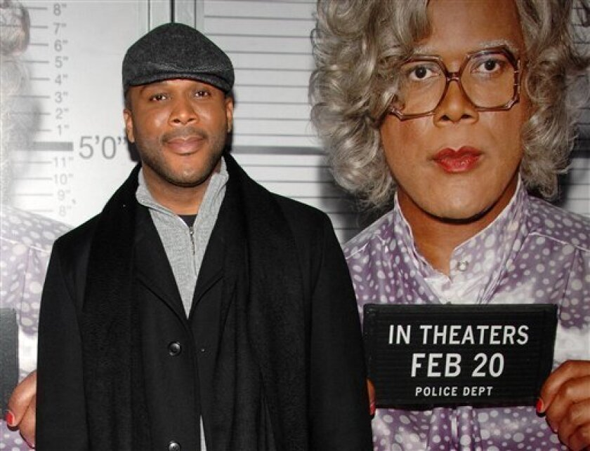 """FILE - In a Wednesday, Feb. 18, 2009 photo, actor Tyler Perry stands next to a poster of his character Madea, whom Perry has said is based on his own mother Willie Maxine Perry, as he attends the premiere of """"Tyler Perry's : Madea Goes to Jail"""" in New York. Tyler announced Tuesday, Dec. 8, 2009 that Willie Maxine Perry has died. She was 64. (AP Photo/Peter Kramer)"""