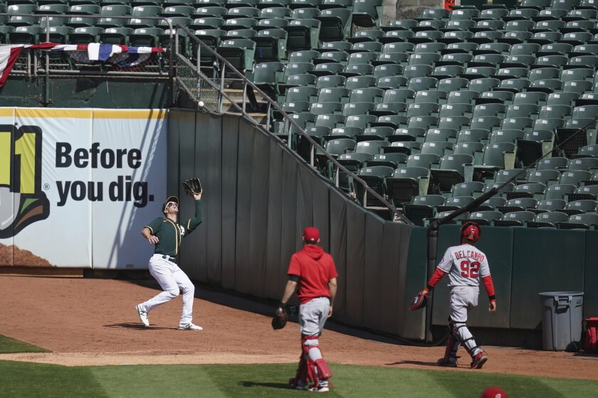 Athletics right fielder Mark Canha catches Taylor Ward's foul out behind the Angels' bullpen Sunday in Oakland.