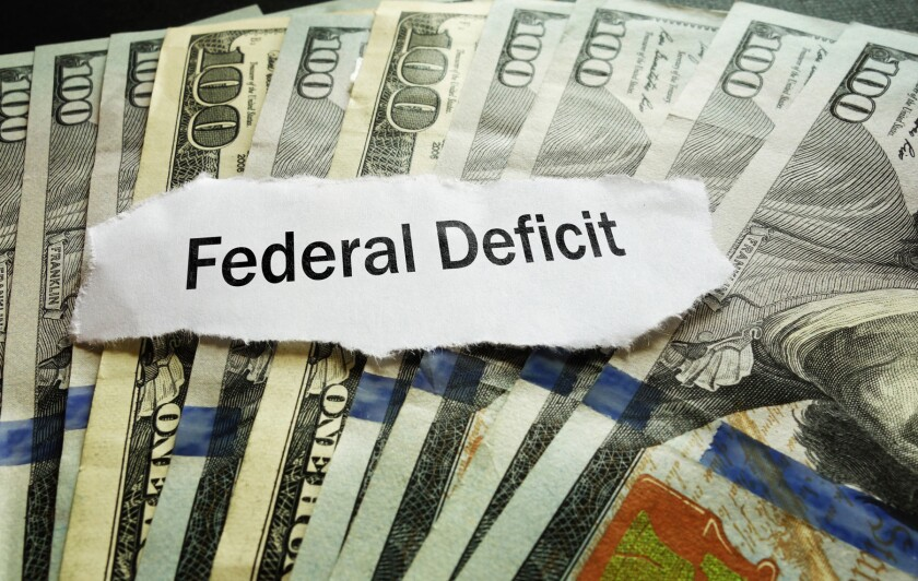 Federal Deficit newspaper headline on hundred dollar bills