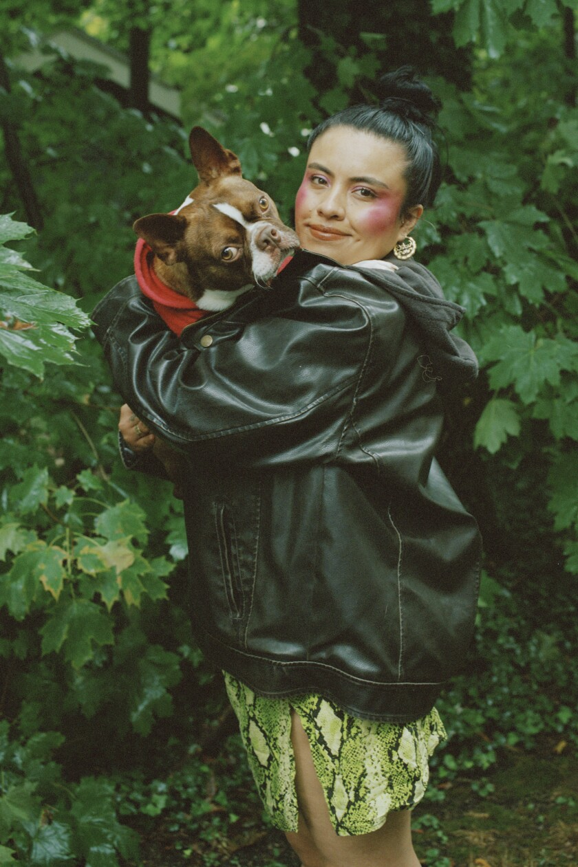 Writer Karla Cornejo Villavicencio holds a dog at her home in New Haven, Conn.