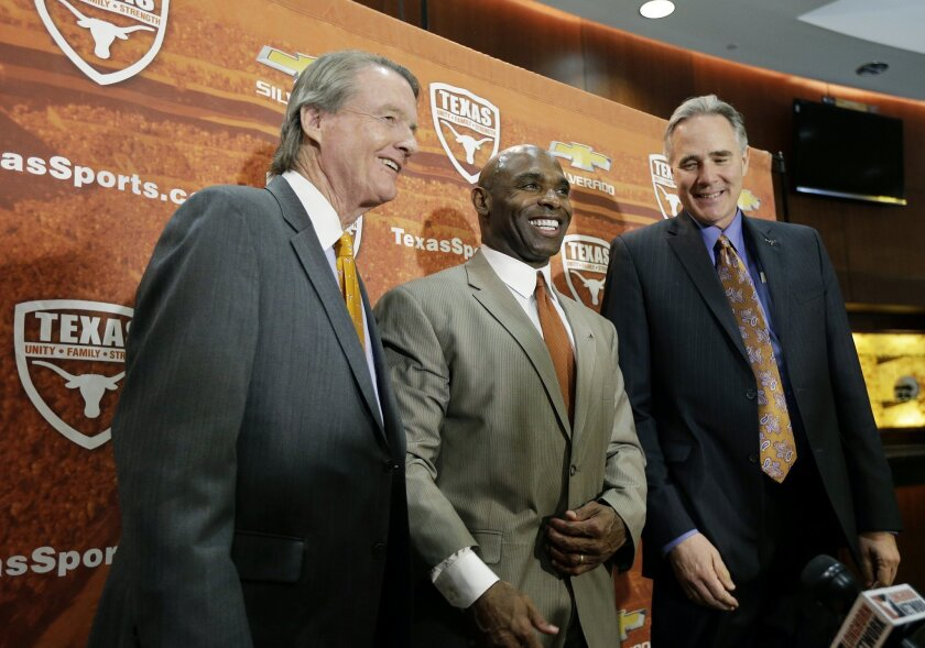 Charlie Strong, center, poses with Texas president Bill Powers, left, and athletic director Steve Patterson, right, following an NCAA college football news conference where he was introduced as the new Texas football coach, Monday, Jan. 6, 2014, in Austin, Texas. Strong takes over for Mack Brown, who stepped down last month after 16 seasons. (AP Photo/Eric Gay)