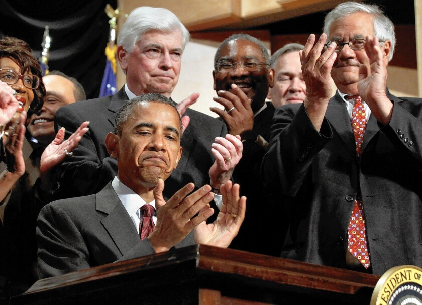 President Obama applauds after signing the Dodd-Frank bill into law during a ceremony with former Sen. Christopher Dodd, center, former Rep. Barney Frank, right, and other members of Congress on July 21, 2010.