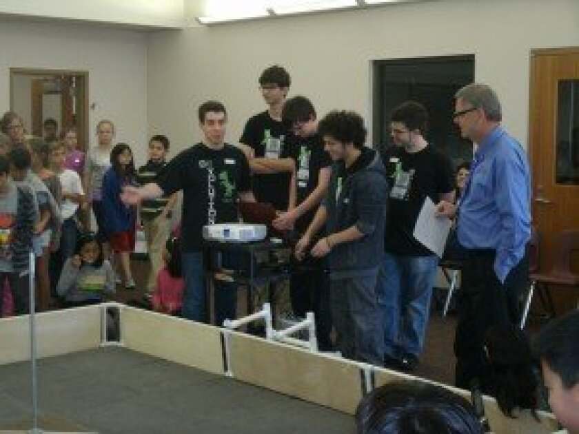 Five De.Evolution team members offer tips to Solana Pacific School Principal Brian McBride on how to drive the robot