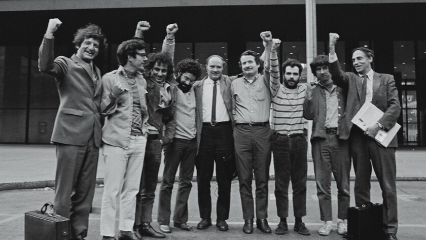Portrait of the Chicago Seven and their lawyers as they raise their fists in unison outside the courthouse where they were on trial for conspiracy and inciting a riot during the 1968 Democratic National Convention, Chicago, Illinois, on October 8, 1969.